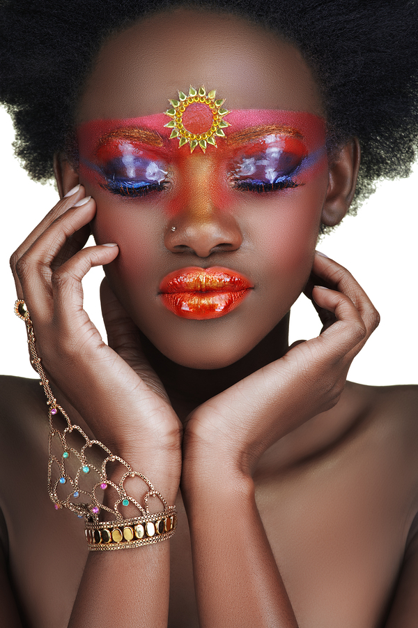 African beauty with glossy and golden make-up holding her face in hands